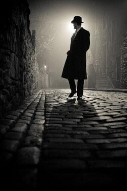 Laurence Winram MAN IN HAT WALKING IN COBBLED STREET