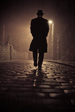 Laurence Winram MAN WALKING IN COBBLED STREET AT NIGHT