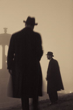 Laurence Winram TWO MEN STANDING BY MONUMENT IN FOG