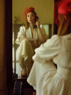 Alexey Kazantsev RETRO WOMAN IN HAT HOLDING TELEPHONE INDOORS
