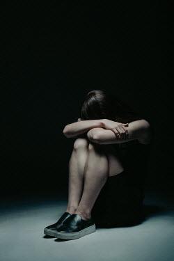 Magdalena Russocka sad teenage girl sitting with arms around knees in shadowy room