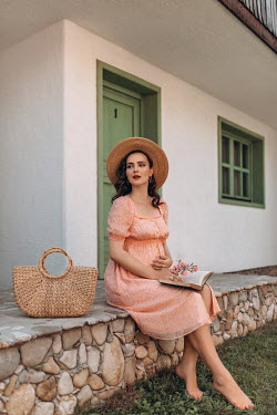 Nadja Berberovic PREGNANT WOMAN WITH BOOK SITTING OUTSIDE COTTAGE