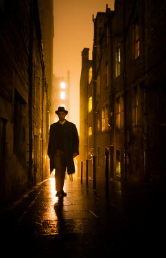 Laurence Winram MAN IN HAT IN CITY STREET AT NIGHT