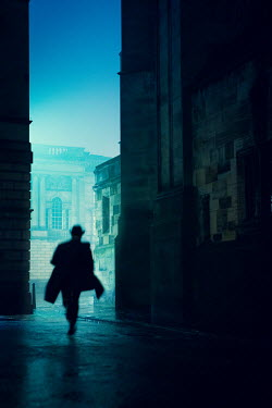 Laurence Winram SILHOUETTED MAN RUNNING IN CITY AT NIGHT