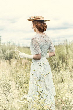 Laurence Winram Young woman in Victorian dress and straw hat in field