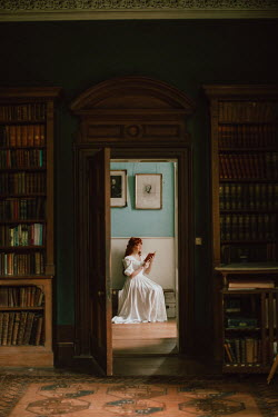 Rebecca Stice WOMAN SITTING BY LIBRARY IN HOUSE READING BOOK