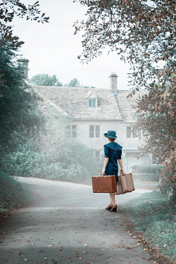 Natasza Fiedotjew RETRO WOMAN WITH SUITCASES OUTSIDE COTTAGE