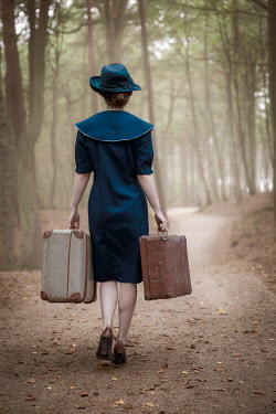 Natasza Fiedotjew Vintage woman carrying suitcases walking on road in woods