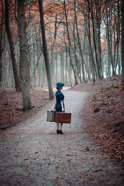 Natasza Fiedotjew Vintage woman carrying suitcases standing on road in woods