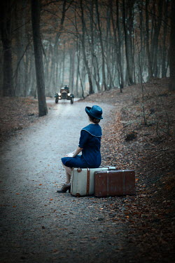 Natasza Fiedotjew Vintage woman sitting on suitcases on road in woods