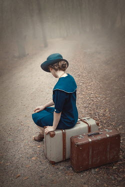 Natasza Fiedotjew Vintage woman sitting on suitcases on countryroad