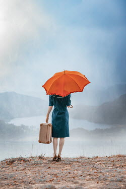 Natasza Fiedotjew Vintage woman with umbrella and suitcase looking at lake in rain