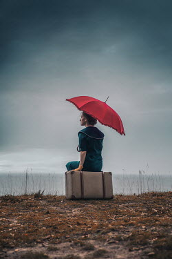 Natasza Fiedotjew Vintage woman with umbrella sitting on suitcase by sea