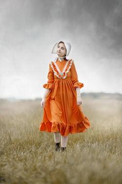 Anna Buczek GIRL IN ORANGE DRESS AND BONNET IN COUNTRYSIDE
