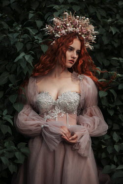 Jovana Rikalo WOMAN WITH RED HAIR AND HEADDRESS IN GARDEN