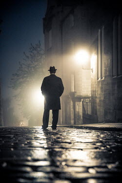 Laurence Winram Man in hat and coat standing on cobblestones at night