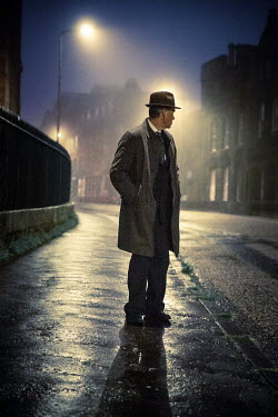 Laurence Winram RETRO MAN STANDING IN CITY STREET AT NIGHT