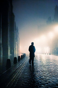 Laurence Winram SILHOUETTED MAN WALKING IN CITY STREET AT NIGHT