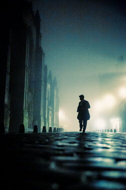 Laurence Winram SILHOUETTED MAN RUNNING IN CITY STREET AT NIGHT