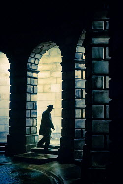 Laurence Winram SILHOUETTED MAN WITH HAT IN ARCHWAY OF BUILDING