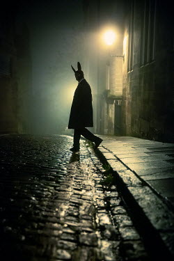 Laurence Winram SILHOUETTED MAN WITH MASK IN CITY STREET AT NIGHT