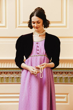 Matilda Delves BRUNETTE REGENCY WOMAN STANDING INDOORS HOLDING PEARLS