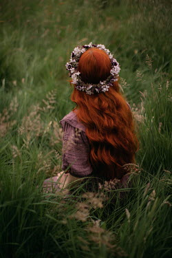 Rebecca Stice WOMAN WITH RED HAIR AND GARLAND SITTING IN FIELD