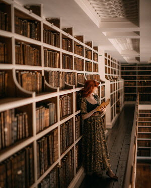 Rebecca Stice WOMAN WITH RED HAIR STANDING BY BOOK SHELVES
