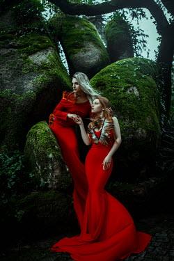 Katerina Klio TWO WOMEN IN RED DRESSES BY ROCKS