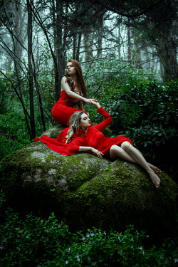 Katerina Klio TWO WOMEN IN RED DRESSES ON LARGE ROCKS