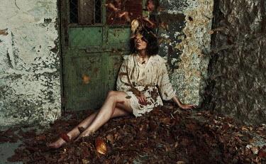 Kirill Sakryukin BAREFOOT WOMAN SITTING OUTSIDE BUILDING IN LEAVES