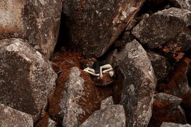 Kirill Sakryukin WOMAN LYING ON LARGE ROCKS