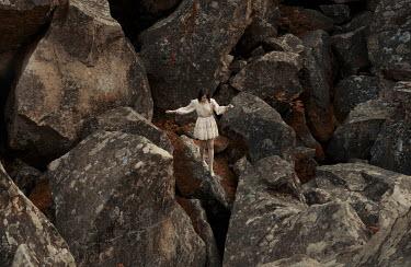 Kirill Sakryukin WOMAN BALANCING ON LARGE ROCKS