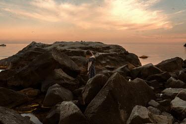 Kirill Sakryukin WOMAN STANDING ON ROCK BY WATER AT SUNSET