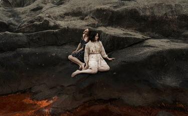 Kirill Sakryukin TWO WOMEN SITTING ON LARGE ROCK
