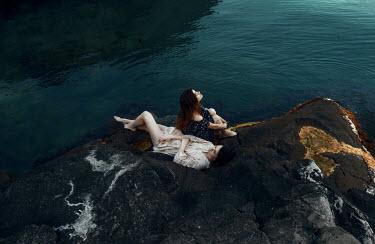 Kirill Sakryukin TWO WOMEN ON LARGE ROCK BY WATER