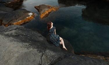 Kirill Sakryukin WOMAN IN WHITE ON ROCK BY WATER