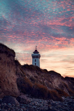 Carmen Spitznagel LIGHTHOUSE ON CLIFF BY BEACH AT SUNSET