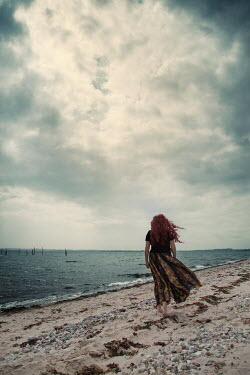 Carmen Spitznagel WOMAN WITH RED HAIR WALKING ON WINDY BEACH