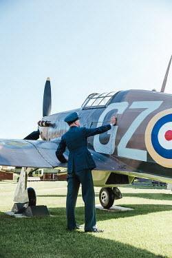 Matilda Delves WARTIME PILOT TOUCHING AEROPLANE ON GROUND