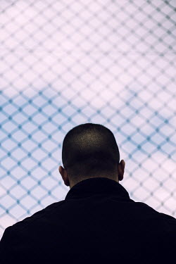 Mohamad Itani MAN WITH SHAVEN HAIR OUTDOORS BY FENCE