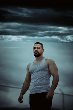 Mohamad Itani MAN STANDING IN PRISON OUTDOORS WITH STORMY SKY