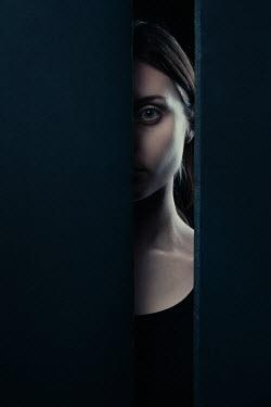 Magdalena Russocka woman staring through gap in wall