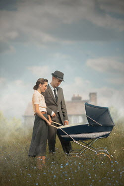 Ildiko Neer Vintage couple with pram in meadow by house
