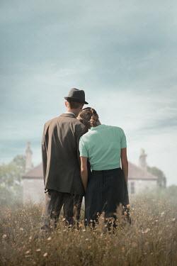 Ildiko Neer Vintage couple standing in meadow by house
