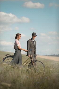 Ildiko Neer Vintage couple walking with bicycle in meadow