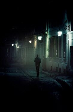 Jaroslaw Blaminsky MAN WALKING IN CITY STREET AT NIGHT