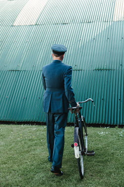Matilda Delves WARTIME PILOT WITH BICYCLE OUTSIDE BUILDING