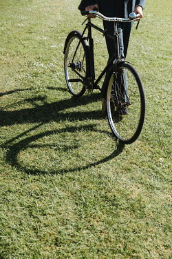 Matilda Delves RETRO MAN PUSHING BICYCLE ON GRASS