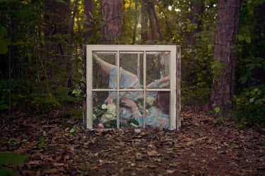 Heather Evans Smith WOMAN WITH FLOWERS TRAPPED BEHIND WINDOW OUTDOORS